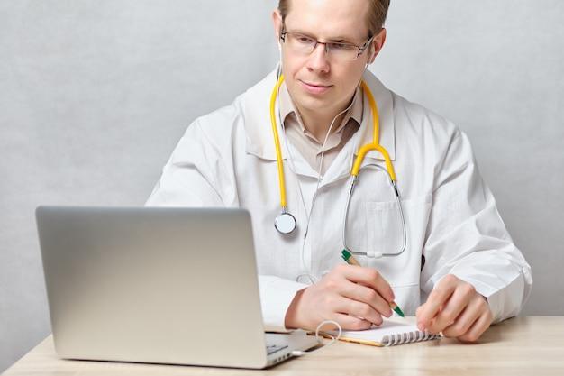 El médico escucha al cliente por videollamada y registra los síntomas.