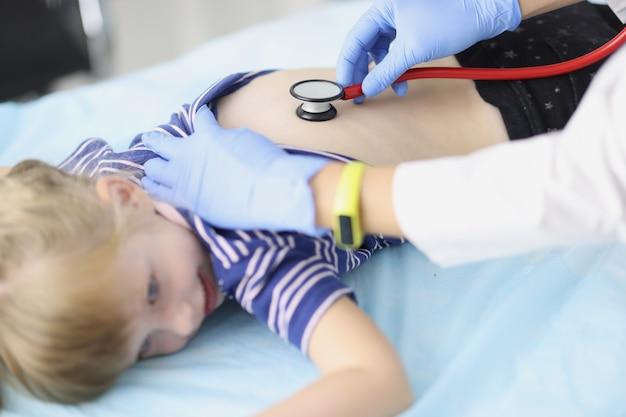 El médico escucha los pulmones de la niña con un estetoscopio. examen por un pediatra. atención médica para niños