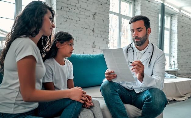 Médico estadounidense hablando con la madre y el niño pequeño.