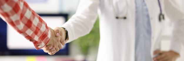 Médico con estetoscopio alrededor del cuello estrechar la mano de los pacientes en la clínica de cerca con éxito