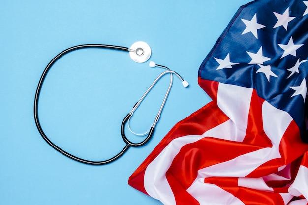Médico estetoscopio y bandera de estados unidos sobre una superficie azul. concepto de medicina de ee. uu., alto nivel, seguro médico, mejor medicina, vacuna, virus, epidemia. vista plana, vista superior