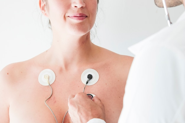 Médico con estetoscopio cerca de mujer con electrodos