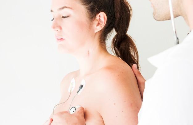 Médico con estetoscopio comprobando la respiración de dama