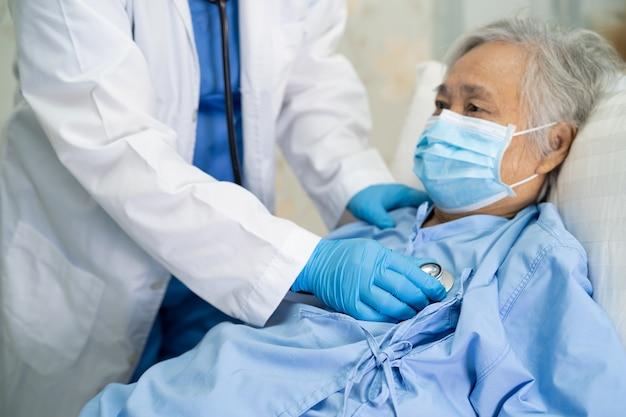 Médico con estetoscopio para controlar a una paciente asiática mayor que usa una mascarilla para proteger el coronavirus covid-19.