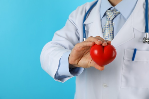 Médico con estetoscopio y corazón contra la superficie azul, espacio de copia