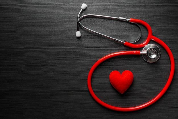 Médico estetoscopio con corazón rojo sobre mesa de madera negra