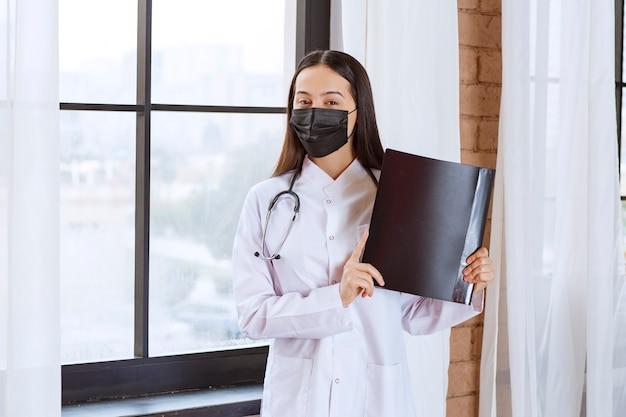 Médico con estetoscopio y máscara negra de pie junto a la ventana y sosteniendo una carpeta de historia negra de los pacientes.