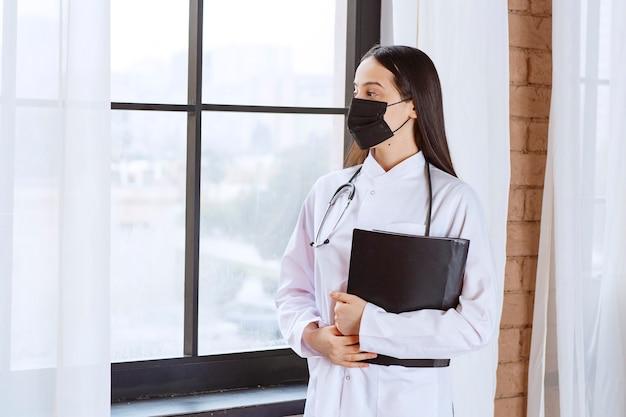 Médico con estetoscopio y máscara negra de pie junto a la ventana y sosteniendo una carpeta de historial negro de los pacientes mientras mira por la ventana.