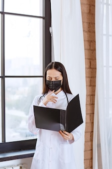Médico con estetoscopio y máscara negra de pie junto a la ventana y sosteniendo una carpeta negra de la historia de los pacientes, revisándola y se ve aterrorizada.