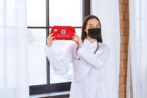 Médico con estetoscopio y máscara negra sosteniendo un botiquín de primeros auxilios rojo.