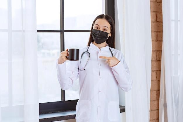 Médico con estetoscopio y máscara negra sosteniendo una taza de bebida negra en el descanso.