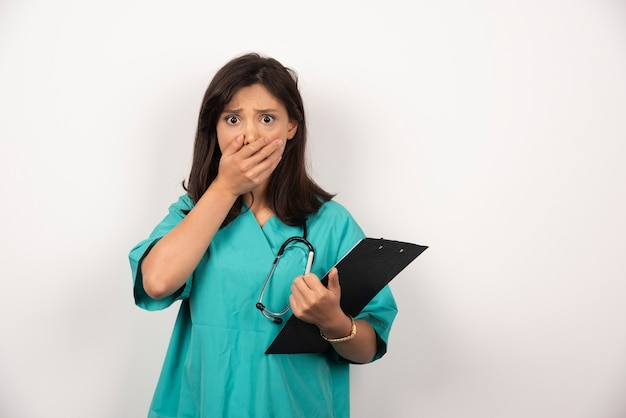 Médico con estetoscopio y portapapeles cubriendo su boca sobre fondo blanco.