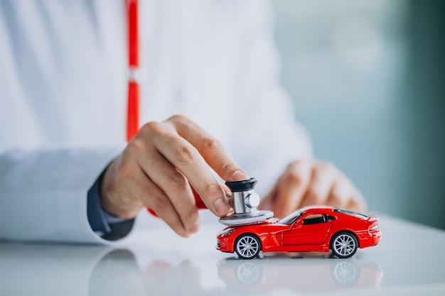 Médico con estetoscopio en una sala de exposición de automóviles