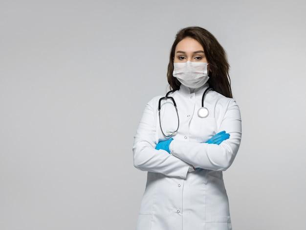 Médico con estetoscopio en uniforme médico blanco, con guantes azules y máscara blanca estéril