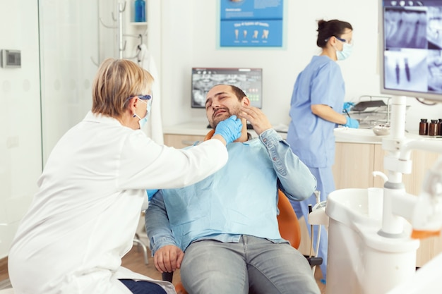 Médico estomatólogo que controla el dolor de dientes del paciente durante la cita de estomatología