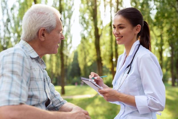 El médico examina al anciano en el parque de verano.