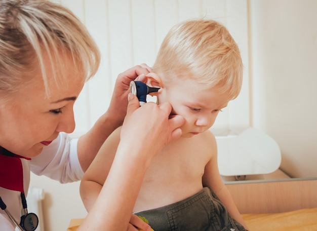 El médico examina el oído con otoscopio en una sala de pediatría.