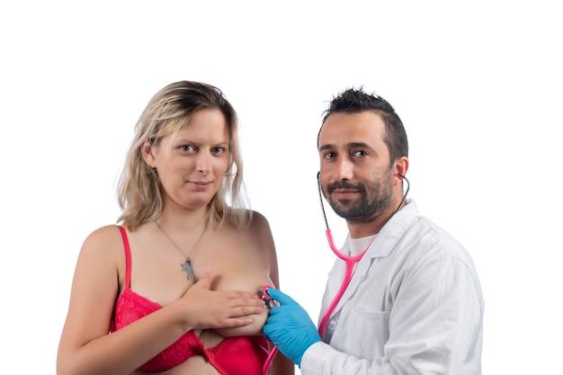 Médico examina el pecho de la mujer con estetoscopio en busca de bultos u otras anomalías