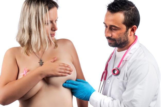 Médico examina el pecho de la mujer con la mano en busca de bultos u otras anomalías