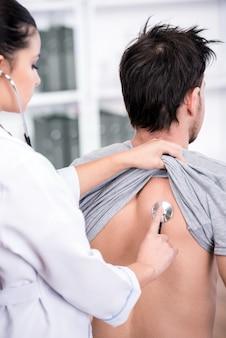 El médico está examinando los pulmones del paciente con un estetoscopio.