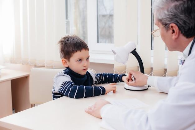 Un médico experimentado escucha y trata a un niño en una clínica moderna. virus y una epidemia