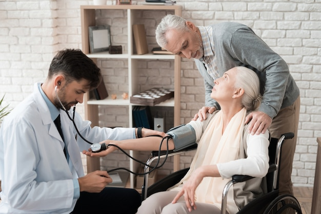 Médico experimentado con tonómetro ayuda anciana.