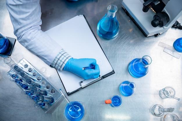 El médico está experimentando en el laboratorio para encontrar un medicamento para prevenir el virus covid-19.