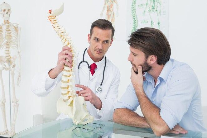 Médico explicando la columna vertebral a un paciente