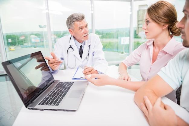 Médico explicando a sus pacientes resultados de análisis.