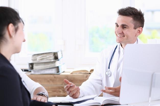 Médico de familia masculino escuchando atentamente a la joven pareja en retrato de oficina.
