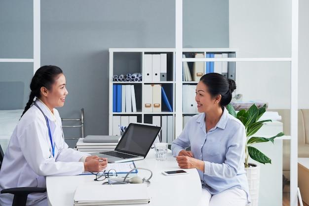 Médico femenino asiático consultar a mujer en oficina