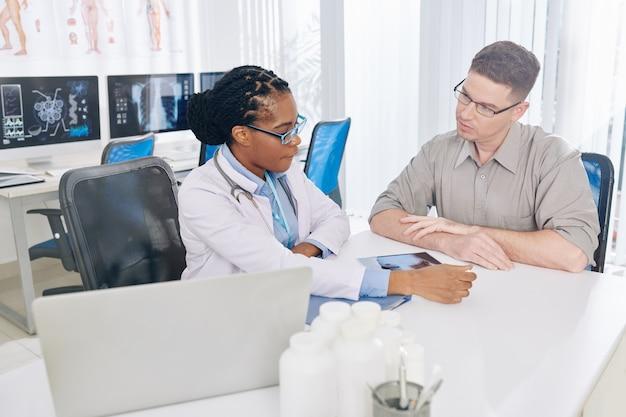 Médico general hablando con el paciente