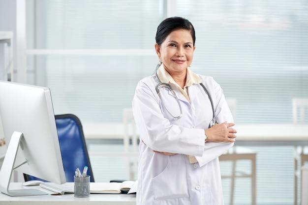 Médico general de pie con los brazos cruzados en el consultorio médico