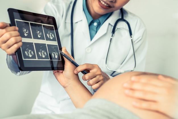 Médico de ginecólogo y mujer embarazada en el hospital