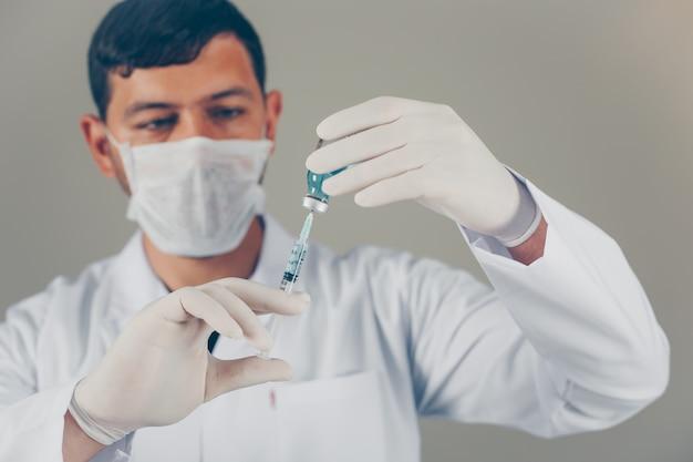 Médico con guantes y máscara rellenando la jeringa en un vial. vista lateral horizontal