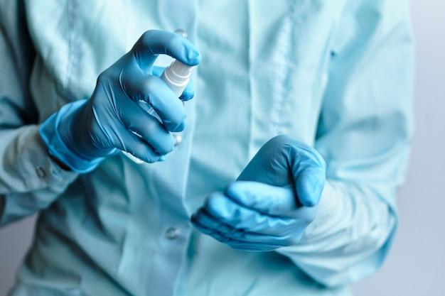 Un médico con guantes médicos azules tiene un desinfectante antiséptico y aerosoles en sus manos, concepto de protección contra el coronavirus covid-19.