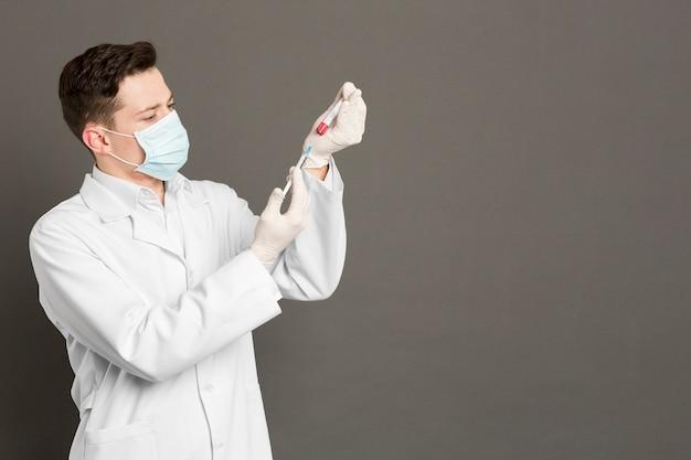 Médico con guantes quirúrgicos y jeringa de llenado de mascarilla con vacuna