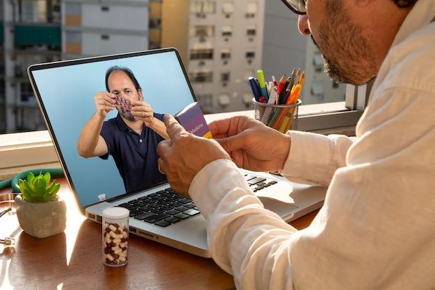 El médico habla con su paciente a través de la telemedicina durante la pandemia de coronavirus en su residencia frente a la ventana