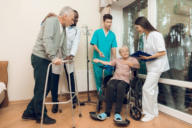 El médico está hablando con una anciana en un asilo de ancianos