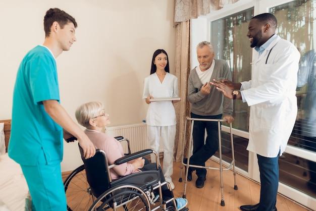 El médico está hablando con una anciana en un hogar de ancianos.