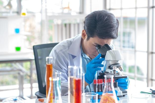 El médico está haciendo un microscopio para la investigación, la vacuna como tratamiento para los resfriados