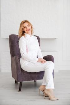 Médico de la hermosa joven en uniforme blanco posando en una silla y mirando a la cámara.