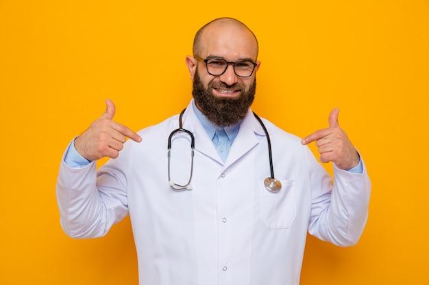 Médico hombre barbudo en bata blanca con estetoscopio alrededor del cuello con gafas mirando sonriendo confiado apuntando a sí mismo