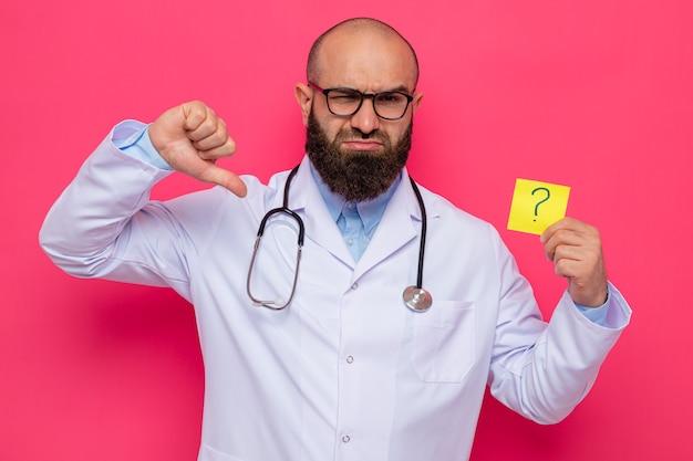 Médico hombre barbudo en bata blanca con estetoscopio alrededor del cuello con gafas sosteniendo papel recordatorio con signo de interrogación con el ceño fruncido mostrando los pulgares hacia abajo