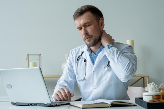 El médico hombre está estresado y cansado por el trabajo duro para cuidar a los pacientes médico masculino cansado después del turno