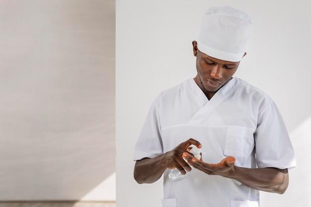 Médico hombre usando desinfectante para manos