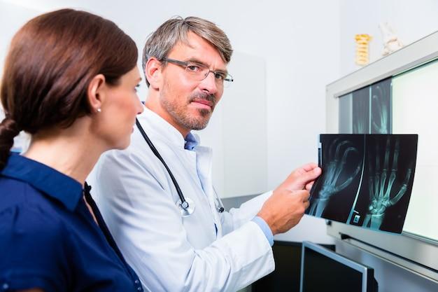 Médico con imagen de rayos x de la mano del paciente en su cirugía examinando la imagen