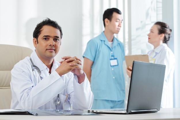 Médico indio trabajando en equipo portátil