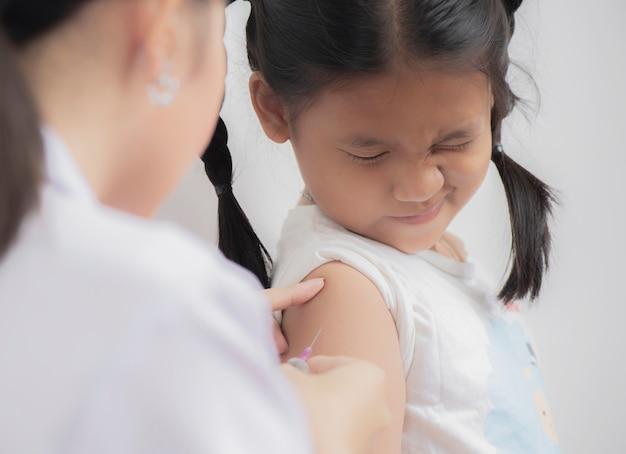 Médico inyectando vacunación en brazo de niña niño