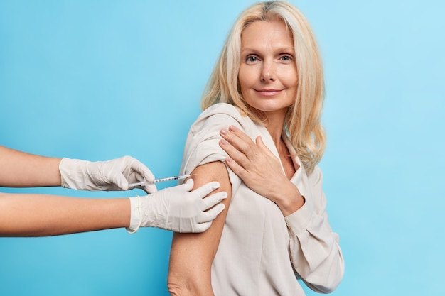 Médico irreconocible con guantes médicos sostiene una jeringa que inyecta la vacuna a una paciente de mediana edad